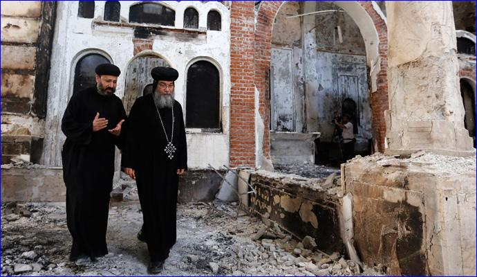 August 26, 2013: Bishop-General Macarius (right), a Coptic Orthodox leader, walks around the damaged Evangelical Church in Minya, south of Cairo (REUTERS/Louafi Larbi).