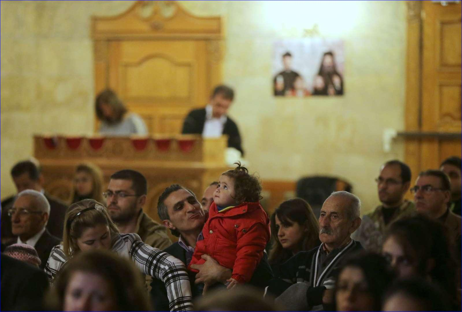 Syrian Christans look on during Divine Liturgy at the Greek Orthodox church in the Syrian government controlled area of Aleppo on November 16, 2014 (AFP).