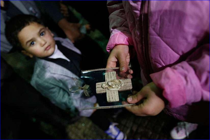 An Iraqi Christian refugee girl holds a souvenir of the Holy Family Dec. 12 as a boy looks on at a church in Hazmiyeh, near Beirut (CNS photo/Jamal Saidi, Reuters).