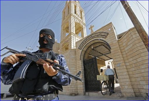 In Iraqi security officer guards a church (Karim Sahib/AFP/Getty Images)