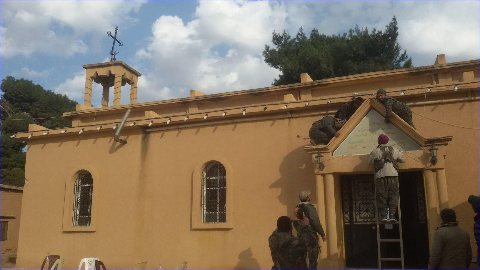 Assyrian fighters mounting the cross on the Church of St. Pithew in Tel Hurmizd (AINA photo).