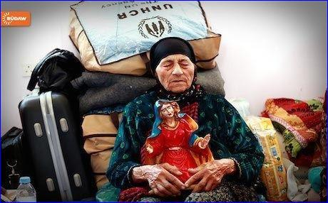 An elderly Christian woman, made homeless by ISIS attacks on the minority in Iraq, sits with her belongings in the Kurdistan Region.