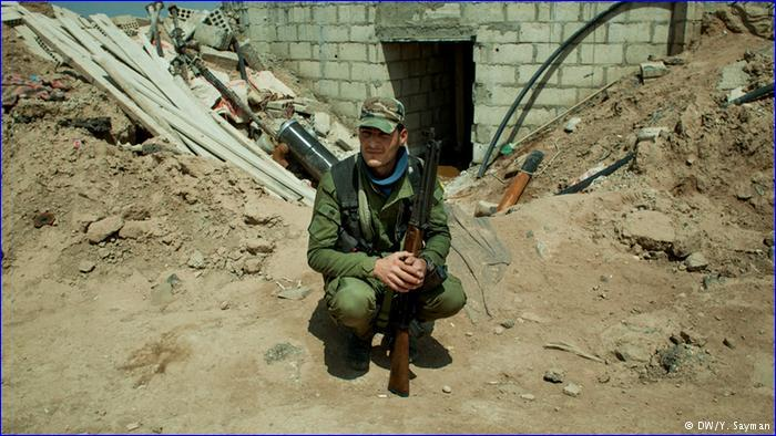 "A Syriac Military Council soldier rests in a position overlooking ""IS"" positions."