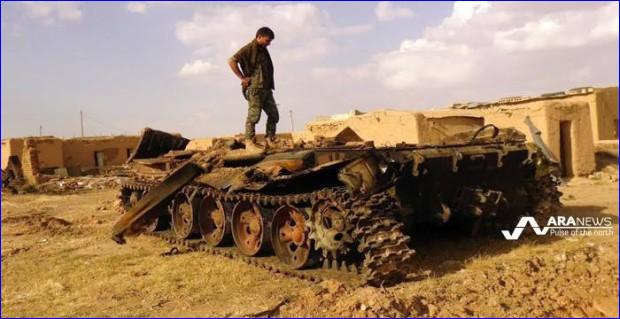 A Kurdish YPG fighter at the top of a destroyed tank, which was hit during clashes with ISIS militants in Hasakah countryside (photo: ARA News).