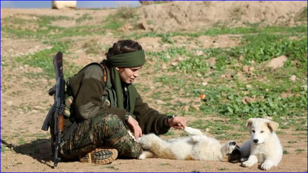 "Assyrian Christian Lucia, member of the battalion called the ""Female Protection Forces of the Land Between the Two Rivers"" fighting the Islamic State group, plays with a dog during a training on December 1, 2015 at their camp in the town of al-Qahtaniyah, near the Syrian-Turkish border (aka Kabre Hyore in Syriac, and Tirbespi in Kurdish) (AFP/DELIL SOULEIMAN)."