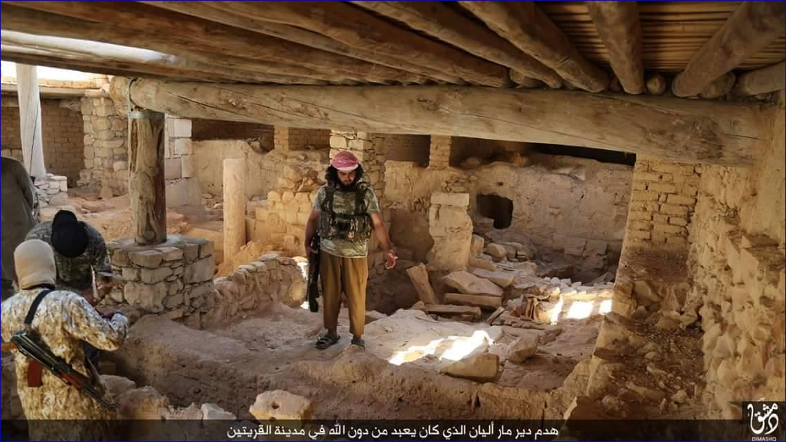 An ISIS fighters stands in the rubble of St. Elian monastery, an Assyrian monastery from the 5th century, after it has been destroyed.